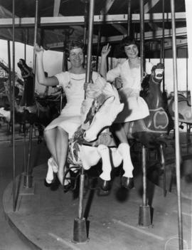 Miss P.N.E. 1958, Sharon Durham, and Miss P.N.E. 1956, Joan Greenwood, on merry-go-round on P.N.E...