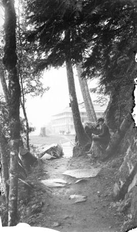 [Man seated at edge of path leading to St. Alice Hotel, Harrison Hot Springs]