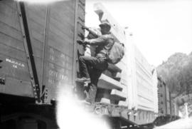 Man climbing onto freight train car
