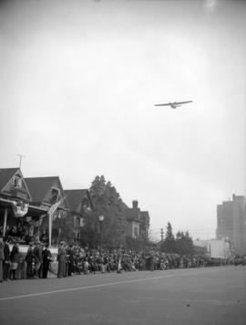 [Airplane flying above military parade along Burrard Street]