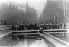 [An unidentified group standing on a reservoir]