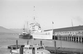 [Royal Navy cruiser and other ship at dock]