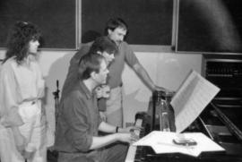 Group at piano in recording studio