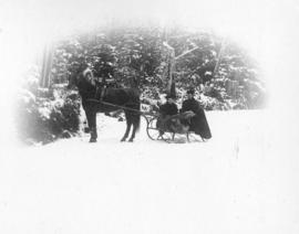 [Two women in a horse-drawn sleigh]