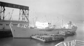 M.S. Nordpol [at dock, with lumber-filled barges alongside]