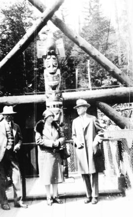 [L.D. Taylor and unidentified man and woman in front of totem pole at the Capilano Suspension Bri...