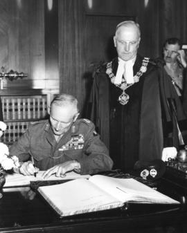 Field Marshal the Viscount Montgomery of Alamein, G.C.B. signing his name to Visitor's Book,...