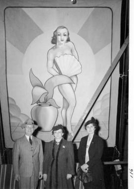 Unidentified fairgoers in front of large painting
