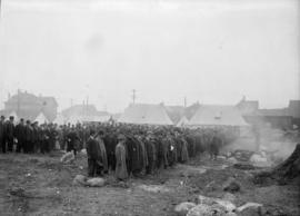 Men lined up on a field, men in uniform present, a pile of objects in front of them