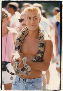 Man carrying snake at Pride Parade