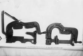Photograph of two different styles of clamp; one made by Bartlett and Son and the other  by Symes