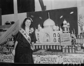 Miss P.N.E., Lynn Adcock, posing with Bettschen's O.K. Apiaries display of honey