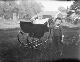 [A child standing beside a baby in a baby carriage]