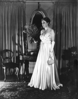 [Full length portrait of] Mrs. A. E. Shane at 3333 Cedar Crescent, Vancouver, in gown worn for op...