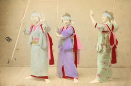 [Studio portrait of three women in traditional Japanese dress holding sticks and a sword]