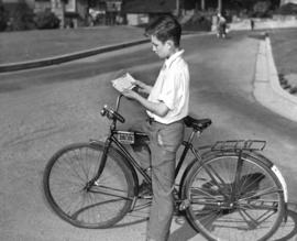 [A boy examines his new bicycle license]
