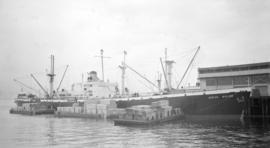 S.S. Ocean Sailor [at dock, with lumber-filled barges alongside]