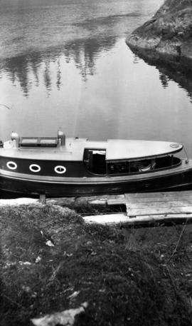 [Unidentified boat at small dock, showing body of water in background]