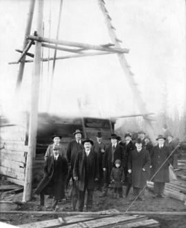 [Group portrait of L.D. Taylor standing with other men in front of a wooden structure with pulleys]