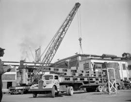 [Crane loading steel structures onto an Arrow Transfer Co. truck at Western Bridge and Steel Fabr...