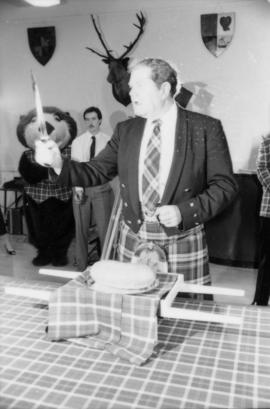 Man wearing kilt about to cut the haggis