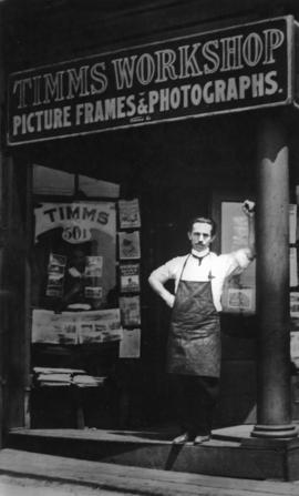 [Timms workshop, 501 West Georgia Street, with Timms standing in doorway]