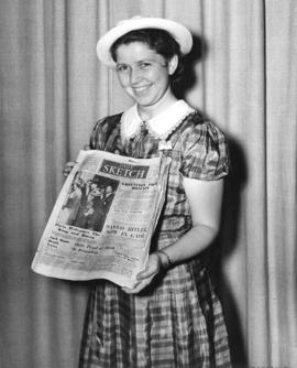 "[Miss Margaret Giles holding a ""Daily Sketch"" newspaper from London, England]"