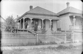 [Family standing on front porch of house in Grandview-Cedar Cottage area]