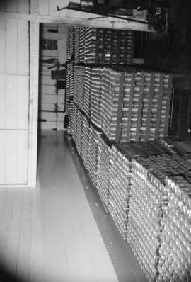 [Cases of unlabelled canned goods on wooden pallets]