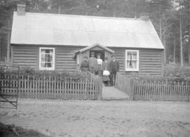 [Unidentified family at the entrance to a house]