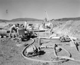 [Ground crew preparing pumps and equipment and mixing fire control chemicals with water for loadi...