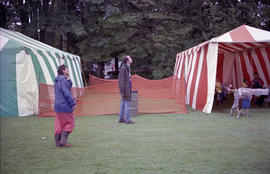 Two people standing between two event tents
