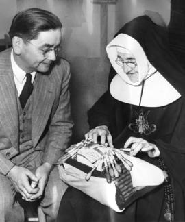 [Sister Mary Joannes shows Dennis Paull how to make lace with a Le Puy bobbin]
