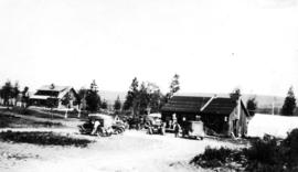 [Board of Trade trip - Automobiles parked in front of small wooden building]
