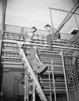 [B.C. Telephone technicians working on telephone line equipment as part of the changeover to a ne...