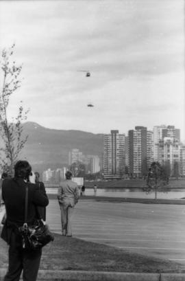 Man photographing helicopter from parking lot