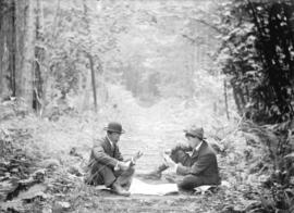 [Two men playing cards in the middle of a logging road in Stanley Park]