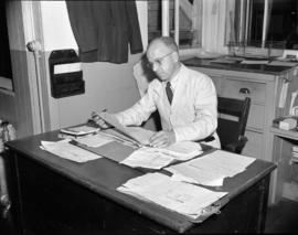[Man seated at desk going over paper work at Kelly Douglas Ltd.]