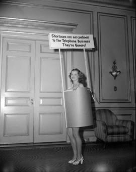[Woman wearing a sign advertising telephone business and other shortages]