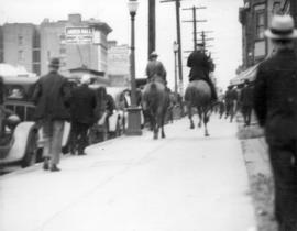 [R.C.M.P. and city police ride towards the Powell Street Riot]
