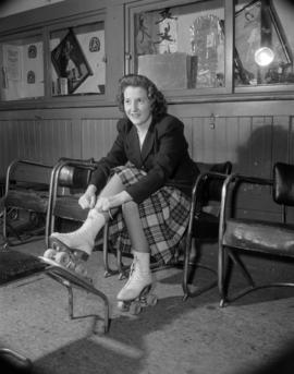 [Woman putting on roller skates at the Vancouver Roller Skating Club]
