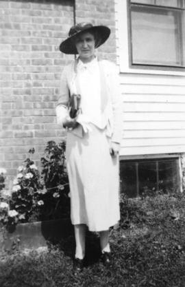 Mrs. E. Newton Drier [standing beside a house]