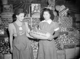 [Two female fruit sellers holding a watermelon decorated to advertise war savings stamps]