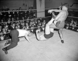 [Wrestlers in the ring in front of an audience of sea cadets]
