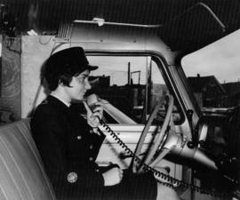 [Female police officer using radio in police vehicle]