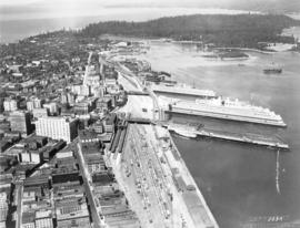 [Aerial view of downtown Vancouver showing showing C.P.R Pier D and Pier B-C looking west to Stan...