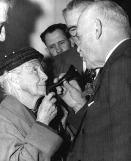 [The Right Honourable Louis St. Laurent speaks into a woman's ear trumpet (hearing aid)]