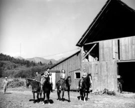 [Visitors on horseback in front of barn at Bowen Island Resort]