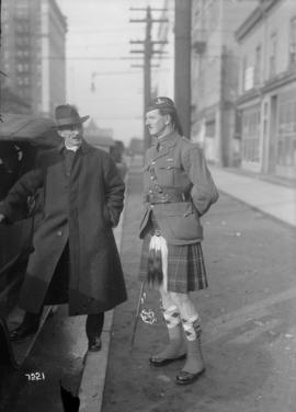 [Two men in the street, one wearing an overcoat, the other a kilt]