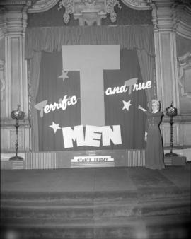 "[Woman pointing to a ""T-Men"" movie display in the lobby of the Orpheum Theatre]"